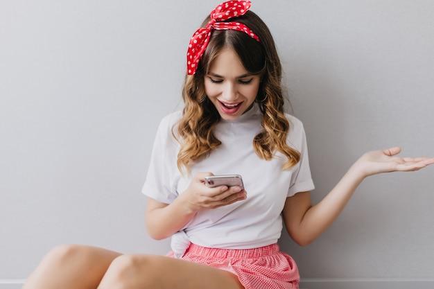 Blithesome schattig meisje in wit t-shirt telefoon scherm kijken. extatische lachende dame met golvend kapsel poseren thuis met smartphone.