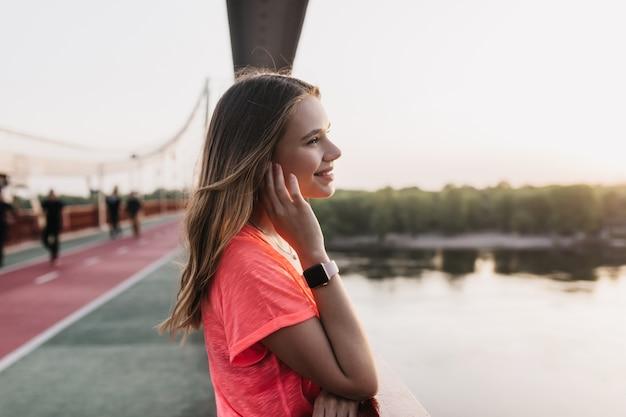 Blithesome sportieve meisje poseren op vervagen aard. buiten foto van verfijnde blonde vrouw genieten van uitzicht op de stad.