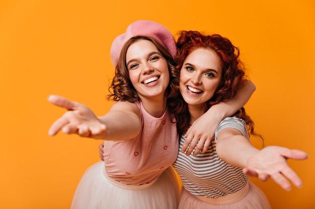 Blithesome vrienden omarmen met een glimlach. studio shot van lachende aantrekkelijke meisjes die zich voordeed op gele achtergrond.