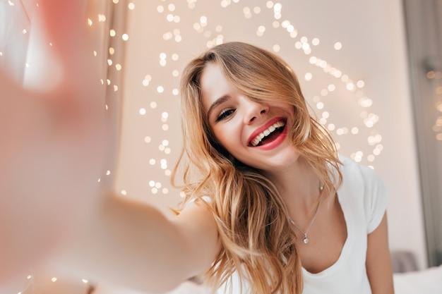 Blithesome vrouw met lang blond haar selfie met glimlach maken. binnen schot van kaukasisch goedgehumeurd meisje dat pret in haar kamer heeft.