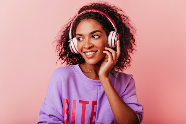 Blithesome zwart meisje luisteren muziek op pastel. winsome afrikaanse vrouw in paarse trui poseren in koptelefoon.