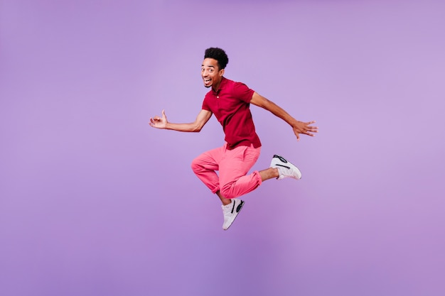 Blithesome zwarte brunette man dansen met een gelukkige glimlach. indoor foto van geïnspireerde man in rode broek en witte schoenen springen.
