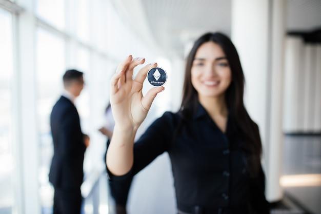 Blockchain en investeringsconcept. bedrijfsvrouwenleider die litecoin voor zijn team met opgeheven handen op bureau houdt.