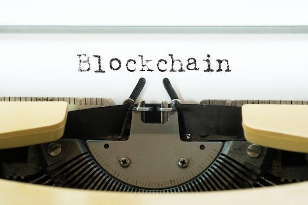 Blockchain getypt op een gele vintage oude typemachine.