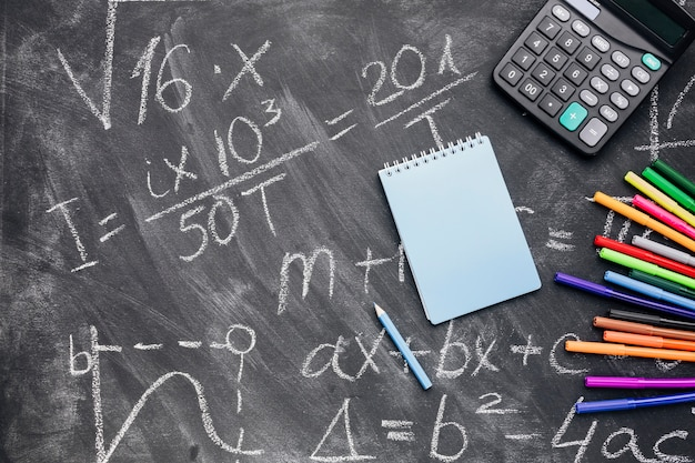 Blocnote en calculator met gevoelde pennen die op geschreven bord worden geschikt