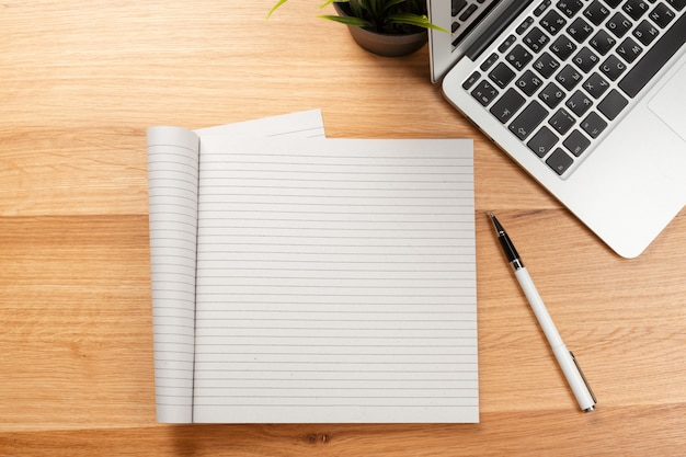 Blocnote en laptop op houten lijst