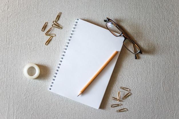 Blocnote en potlood op een grijze achtergrond.