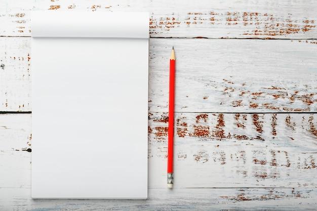 Blocnote met een rood potlood op een witte houten lijst tegen