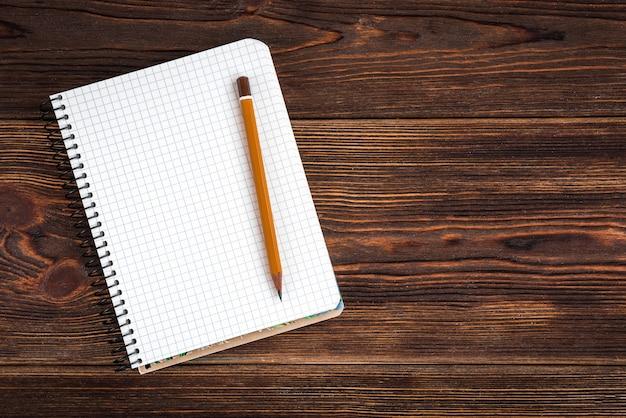 Blocnote met geel potlood en koffie op houten achtergrond. doelen voor het nieuwe jaar. planning en planning concept. te doen lijst.