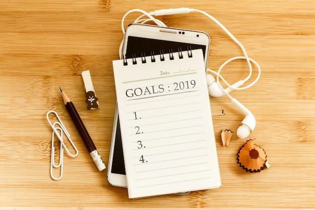 Blocnote met potlood en een slimme telefoon op houten lijst voor het concept van doelen 2019 van het nieuwjaar