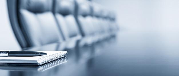 Blocnote op een lijst met pen vóór vergadering, blauwe toon, bedrijfsconcept met exemplaarruimte