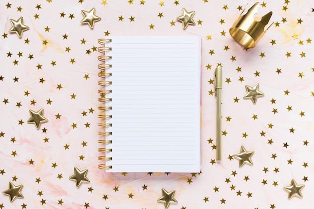 Blocnote, pen, gouden kroon en sterrendecoratie op de werkruimte van het vrouwenbureau, roze achtergrond. wintervakantie vakantie voorbereiding en levensstijl concept. takenlijstsjabloon. plat leggen, bovenaanzicht, kopie ruimte