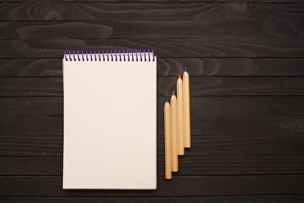 Blocnotes potloden tekengereedschappen houten tafel. hoge kwaliteit foto