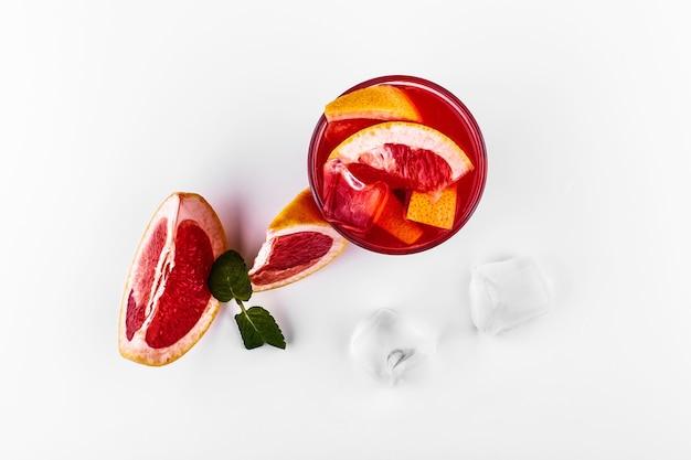 Bloed oranje gin-tonic cocktail geserveerd met plakjes sinaasappel en ijs in een glas