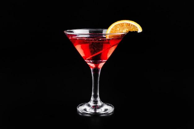 Bloed oranje gin-tonic cocktail geserveerd met plakjes sinaasappel in een glas