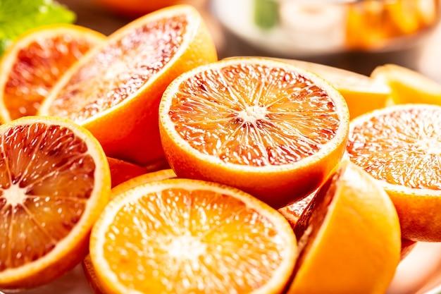 Bloed siciliaanse sinaasappelen gesneden met verse melissa - close-up.