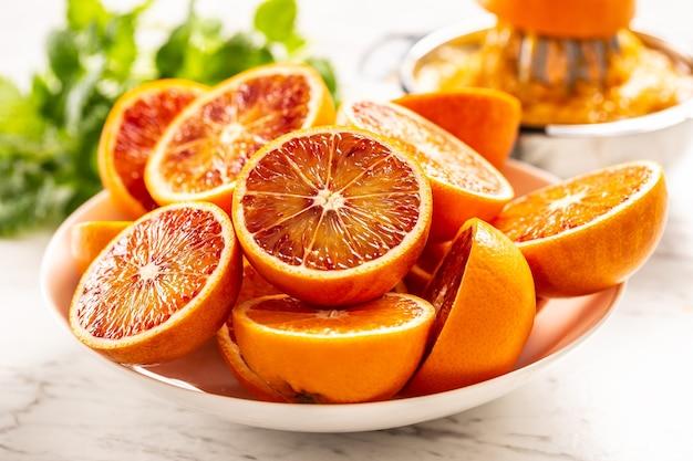 Bloed siciliaanse sinaasappelen gesneden op witte plaat met verse melissa.