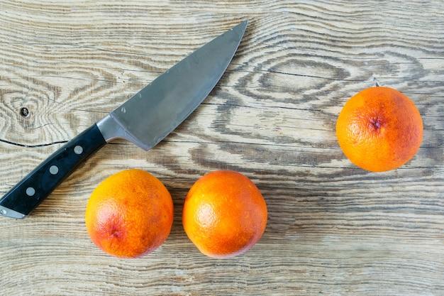 Bloed siciliaanse sinaasappelen op houten snijplank met mes