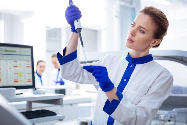 Bloed test. ervaren aansprekende vrouwelijke laboratoriummedewerker die vloeistof meet tijdens het onderzoeken en poseren in het laboratorium