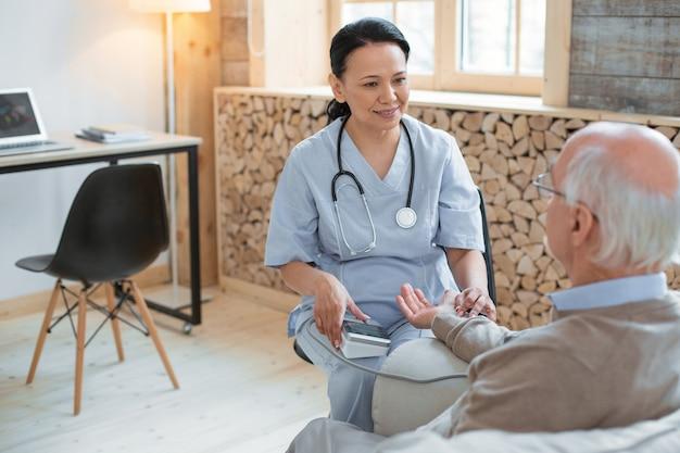 Bloeddruk. bekwame ervaren arts zittend op een stoel tijdens het gebruik van tonometer en het helpen van senior man
