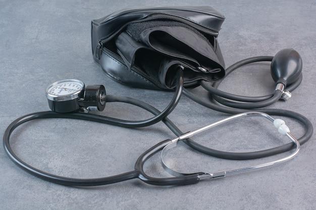 Bloeddrukmeter en stethoscoop op marmeren tafel.