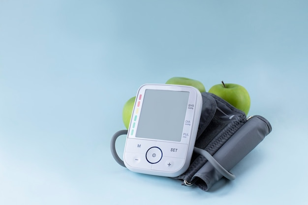 Bloeddrukmeter en verse groene appels. gezonde levensstijl en preventie van hypertensie concept