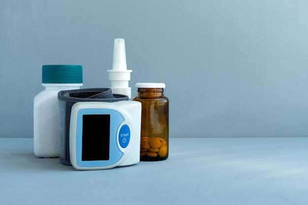 Bloeddrukmeter, medicijnen en pillen op blauwe achtergrond. gezondheidszorg arts concept. ruimte kopiëren.