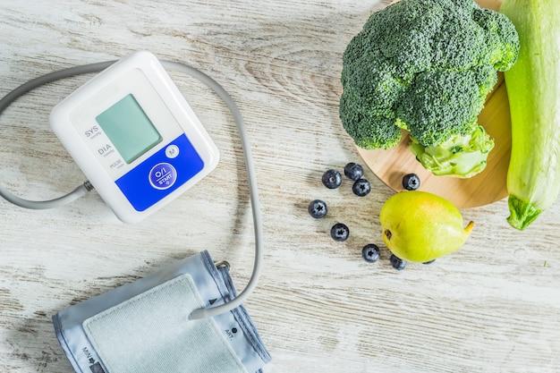 Bloeddrukmeter op een tafel naast tafel met groene groenten en fruit