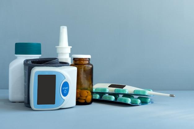 Bloeddrukmeter, thermometer, medicijnen en pillen op blauw