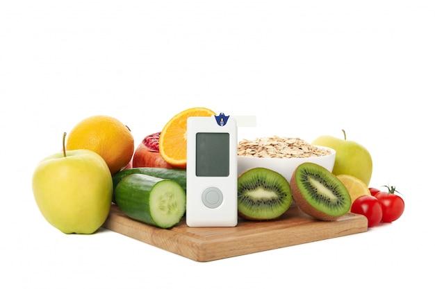 Bloedglucosemeter en dieetvoedsel dat op witte achtergrond wordt geïsoleerd