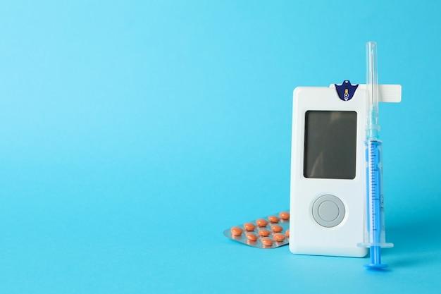 Bloedglucosemeter, spuit en pillen op blauwe achtergrond