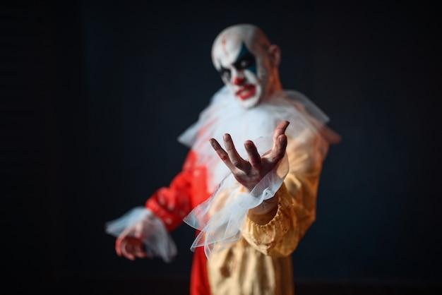 Bloedige clown die met zijn handen naar het slachtoffer reikt