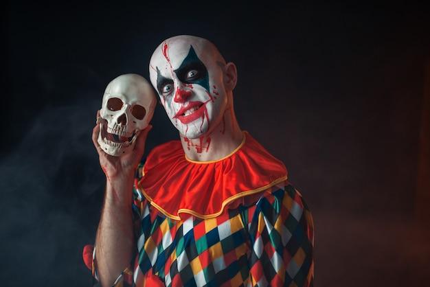 Bloedige clown met gek gezicht houdt menselijke schedel vast