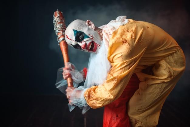 Bloedige clown met gekke ogen houdt honkbalknuppel vast