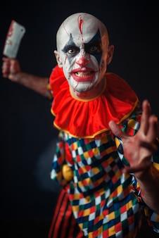 Bloedige clown met vleesmes en honkbalknuppel