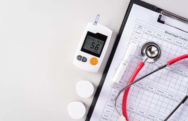 Bloedonderzoek set en suiker tracker record met stethoscoop.