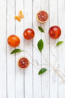 Bloedsinaasappelvruchten in de vorm van ballons op koorden op witte houten achtergrond