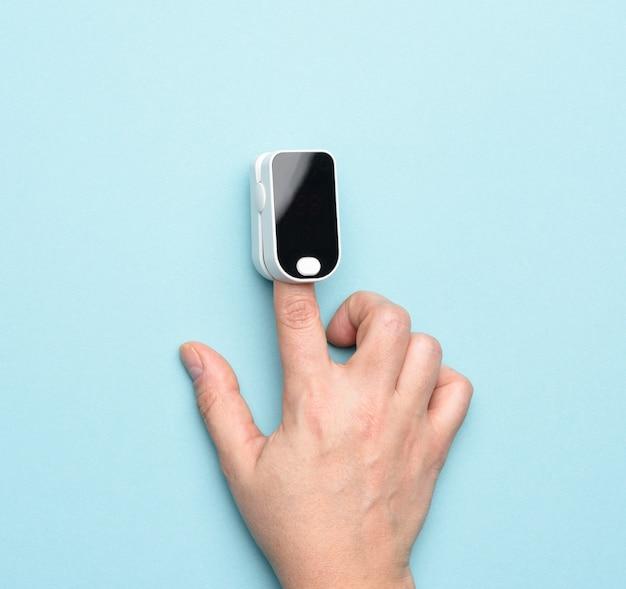 Bloedzuurstofniveau controleren met een draagbare oximeter, blauwe achtergrond