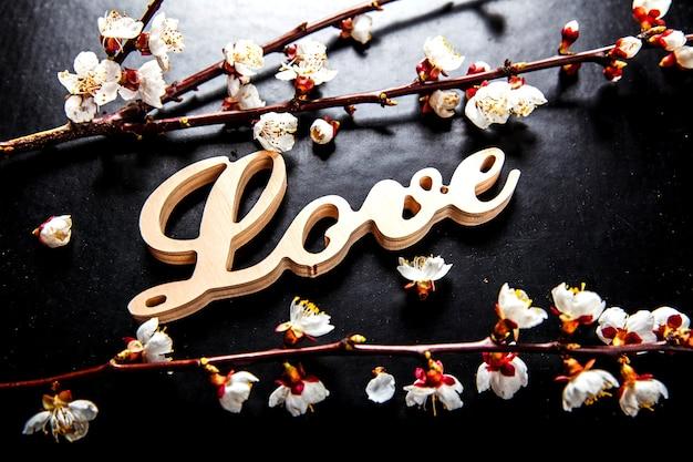 Bloei op een zwarte tafel en een houten bord met het woord liefde