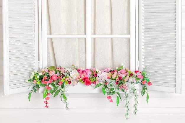 Bloeiend bloembed onder het venster. vensterbank met bloemen