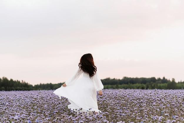 Bloeiend veld van de provence. het meisje is blij en lacht terwijl ze door het bloeiende veld rent.