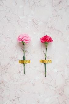 Bloeiende roze anjerbloem geplakt op een marmeren achtergrond