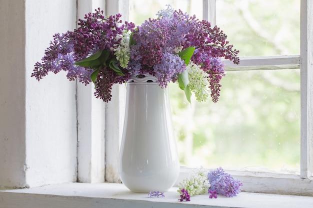 Bloeiende tak van lila bij het raam