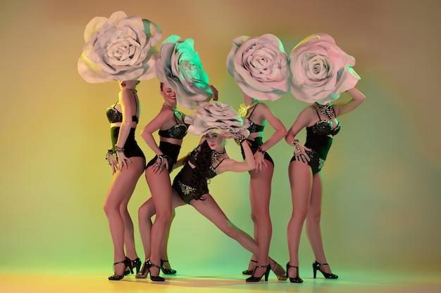 Bloeiende tuin. jonge danseressen met enorme bloemenhoeden in neonlicht op gradiëntmuur.