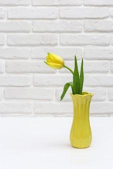 Bloeiende tulp bloemen in kleine gele vaas op witte bakstenen muur in de kamer. boeket bloemen als lentegeschenk voor dames of moederdag. verticaal formaat.
