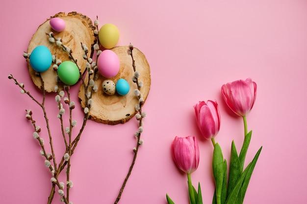 Bloeiende wilgentak, tulpen en paaseieren op houten onderzetters, roze achtergrond