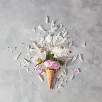 Bloeiende witte en roze pionen, toppen, groen blad in een wafer kegels met bloemblaadjes op een grijze stenen achtergrond,