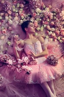 Bloeiende ziel. bovenaanzicht van mooie jonge vrouw in roze ballet tutu omgeven door bloemen. lentestemming en tederheid in koraallicht. kunst foto. concept van de lente, bloesem en het ontwaken van de natuur.