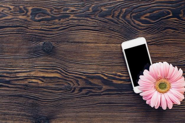 Bloem en mobiele telefoon met een leeg scherm op hout, bovenaanzicht. bespotten