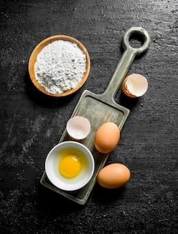 Bloem en verse eieren op zwarte rustieke tafel